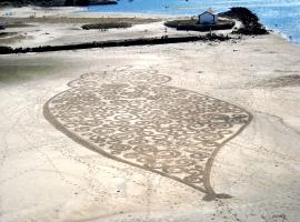 vergängliche Kunst auf dem Jakobsweg: in den Sand gemalte Muster am Strand