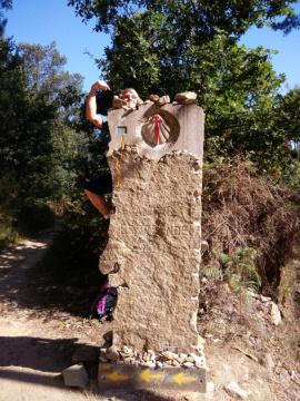 Eine Wegmarkierung auf dem Jakobsweg, an der Pilger Steine ablegen als Symbol für innere Lasten.